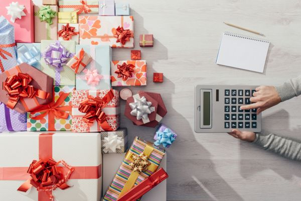 Man calculating costs with a calculator and lots of colorful gift boxes, expensive Christmas concept