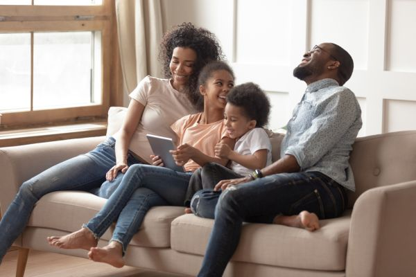 Pre-teen daughter enjoy time with mum dad brother african family sit on couch with tablet having fun using online new apps, internet entertainments, parental control wireless modern tech user concept