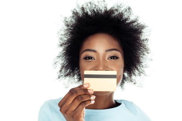 African American woman against a white background holding a credit card in front of her mouth