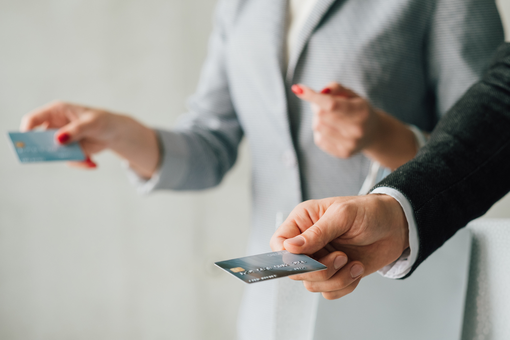 two people holding credit cards